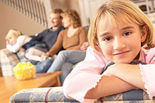 Portrait of girl leaning on arm of couch with family in background.